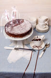 Festivee Cake with chocolate glaze on table served with white crockery Royalty Free Stock Photos