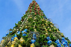 Festively decorated Christmas tree, standing on the street. View from below against the blue sky Royalty Free Stock Photos