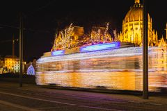 Festively decorated light tram ,Fenyvillamos, on the move with Parliament of Hungary at Kossuth square by night. Christmas season royalty free stock images