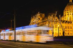 Festively decorated light tram ,Fenyvillamos, on the move with Parliament of Hungary at Kossuth square by night. Christmas season stock photos