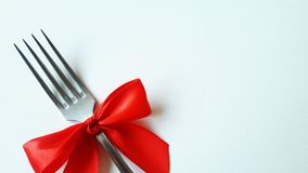 Festively decorated. white leather surface . Insert the text. Photo for the menu of cafe, restaurant, dining room,. A fork with a red bow lies on the white royalty free stock image