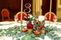 Festively dekorerad banketttabell i restaurangen Nya blommor ?r guld- stearinljus och r?da stolar och granatr?tt dyrt rikt royaltyfri fotografi