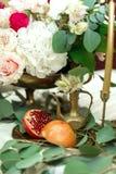 Festively dekorerad banketttabell i restaurangen Nya blommor ?r guld- stearinljus och r?da stolar och granatr?tt dyrt rikt arkivfoto