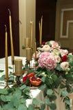 Festively dekorerad banketttabell i restaurangen Nya blommor ?r guld- stearinljus och r?da stolar och granatr?tt dyrt rikt arkivbilder