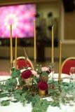 Festively dekorerad banketttabell i restaurangen Nya blommor ?r guld- stearinljus och r?da stolar och granatr?tt dyrt rikt royaltyfri bild