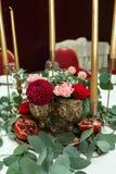 Festively dekorerad banketttabell i restaurangen Nya blommor ?r guld- stearinljus och r?da stolar och granatr?tt dyrt rikt fotografering för bildbyråer