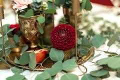 Festively dekorerad banketttabell i restaurangen Nya blommor ?r guld- stearinljus och r?da stolar och granatr?tt dyrt rikt royaltyfria bilder