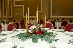 Festively dekorerad rund banketttabell i restaurangen Nya blommor ?r guld- stearinljus och r?da stolar dyrt rikt arkivfoto