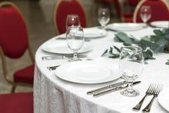 Festively dekorerad rund banketttabell i restaurangen Nya blommor ?r guld- stearinljus och r?da stolar dyrt rikt royaltyfri bild