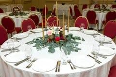 Festively dekorerad rund banketttabell i restaurangen Nya blommor ?r guld- stearinljus och r?da stolar dyrt rikt royaltyfri foto