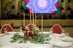 Festively dekorerad rund banketttabell i restaurangen Nya blommor ?r guld- stearinljus och r?da stolar dyrt rikt royaltyfria bilder
