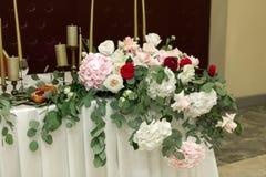 Festively dekorerad rund banketttabell i restaurangen Nya blommor ?r guld- stearinljus och r?da stolar dyrt rikt arkivbilder