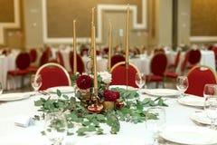 Festively dekorerad rund banketttabell i restaurangen Nya blommor ?r guld- stearinljus och r?da stolar dyrt rikt royaltyfri fotografi