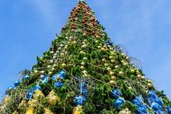 Festively verfraaide Kerstboom, die zich op de straat bevinden Mening van onderaan tegen de blauwe hemel Royalty-vrije Stock Foto's