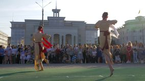 Festividades nacionais, grupo de moças nos trajes tradicionais que dançam na rua da cidade antes dos espectadores da multidão sob video estoque