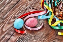 Festività di Pasqua, uova di Pasqua dipinte, canestro decorato con i nastri Fotografia Stock Libera da Diritti