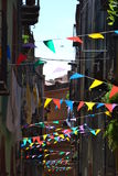 Festivity flags in the town. Colorful sunlit festivity flags decorating a historical town street Stock Photo