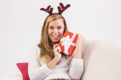 Festliche blonde Entspannung auf Sofa mit Geschenk Lizenzfreie Stockfotos