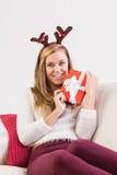 Festliche blonde Entspannung auf Sofa mit Geschenk Stockfoto