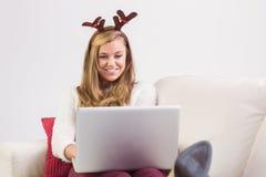 Festliche blonde Entspannung auf Sofa mit Laptop Stockfotos