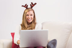 Festliche blonde Entspannung auf Sofa mit Laptop Lizenzfreie Stockbilder