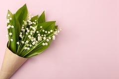 Festliche Blumenmaiglöckchenzusammensetzung im Handwerkshorn auf dem Pastellrosahintergrund Obenliegende Ansicht, Könnenlilienblu Lizenzfreies Stockbild