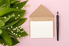 Festliche Blumenmaiglöckchenzusammensetzung und Einladung auf Handwerksumschlag und Kalligraphiestift mit Tinte auf dem Pastellro Stockbild