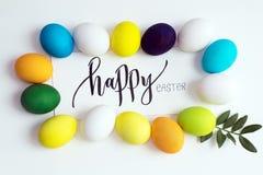 Festliche bunte Eier Ostern auf einem weißen Hintergrund mit einem Grußkarten-Kalligraphie ` glücklichen Ostern-` Eier Gelb, Blau Stockfoto