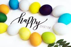 Festliche bunte Eier Ostern auf einem weißen Hintergrund mit einem Grußkarten-Kalligraphie ` glücklichen Ostern-` Eier Gelb, Blau Lizenzfreie Stockbilder