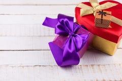 Festliche Geschenkboxen auf weißem hölzernem Hintergrund Stockfotografie