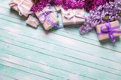 Festliche Geschenkboxen mit Geschenken und lila Blumen auf Türkis Lizenzfreie Stockfotos