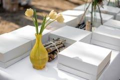 Festliche Hochzeitstafel bedeckt mit der weißen Tischdecke gedient mit Lebensmittelkästen und mit Baumasten verziert Stockfotos
