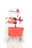 Festliche junge Frau, die Stapel von Geschenken hält Stockfotografie