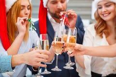 Festliche Leute der Nahaufnahme, die mit Getränken auf einem neuen Jahr auf einem unscharfen Hintergrund zujubeln Kopieren Sie Ra stockbild