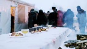 Festliche Tabelle des neuen Jahres mit heißem Tee und Kuchen vor blured Menge stock footage