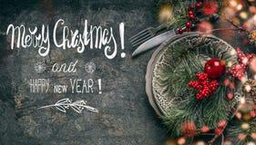 Festliche Tabellengedeckdekoration auf dunklem rustikalem Hintergrund mit Textbeschriftung: Frohe Weihnachten und guten Rutsch in stockfotos