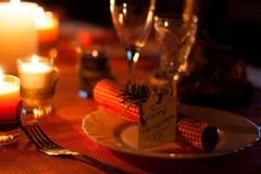 Festliche Zusammensetzung mit Kerzen und Platten Die Serviette auf der Platte Ein schönes Gedeck, rote Tischdecke, Tischdecke in  Lizenzfreie Stockfotos
