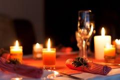 Festliche Zusammensetzung mit Kerzen und Platten Die Serviette auf der Platte Ein schönes Gedeck, rote Tischdecke, Tischdecke im  Lizenzfreie Stockfotografie