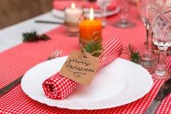Festliche Zusammensetzung mit Kerzen und Platten Die Serviette auf der Platte Ein schönes Gedeck, rote Tischdecke, Tischdecke im  Lizenzfreies Stockbild