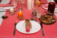 Festliche Zusammensetzung mit Kerzen und Platten Die Serviette auf der Platte Ein schönes Gedeck, rote Tischdecke, Tischdecke im  Stockfoto