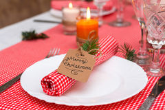 Festliche Zusammensetzung mit Kerzen und Platten Die Serviette auf der Platte Ein schönes Gedeck, rote Tischdecke, Tischdecke im  Stockbild