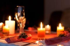 Festliche Zusammensetzung mit Kerzen und Platten Die Serviette auf der Platte Ein schönes Gedeck, rote Tischdecke, Tischdecke in  Stockbild