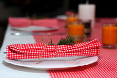 Festliche Zusammensetzung mit Kerzen und Platten Die Serviette auf der Platte Ein schönes Gedeck, rote Tischdecke, Tischdecke im  Stockfotografie