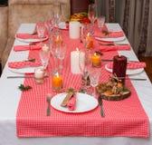 Festliche Zusammensetzung mit Kerzen und Platten Die Serviette auf der Platte Ein schönes Gedeck, rote Tischdecke, Tischdecke im  Lizenzfreie Stockfotos