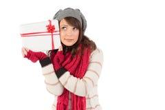 Festlicher Brunette, der weißes und rotes Geschenk hält Stockfotografie