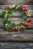 Festlicher grüner Winter Weihnachtskranz an verwittertem Blockhauswandhintergrund Stockfotografie