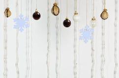 Festlicher Hintergrund gemacht von den Weihnachtsdekorationen, die an einem Seil auf weißem Hintergrund hängen stockbild