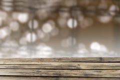 Festlicher Hintergrund mit goldenen Lichteffekten und leerer Holztisch für eine Weihnachtsdekoration stockfoto