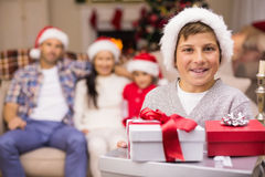 Festlicher Sohn, der Stapel von Geschenken mit seiner Familie hinten hält Stockfotos