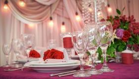 Festlicher Tischschmuck mit roten Blumen und Gläsern lizenzfreie stockfotografie